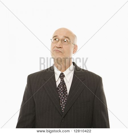 Caucasian middle-aged businessman looking indecisive standing against white background.
