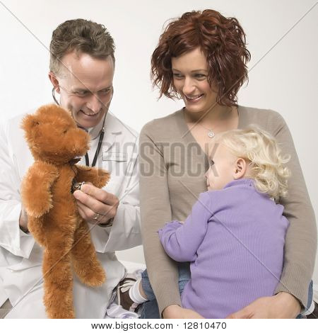 Middle-aged adult Caucasian male doctor holding stethoscope to teddy bear while Caucasian mother and daughter watch.