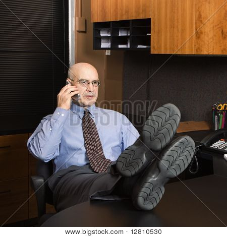 Caucasian middle-aged businessman in office sitting with feet on desk talking on cellphone.