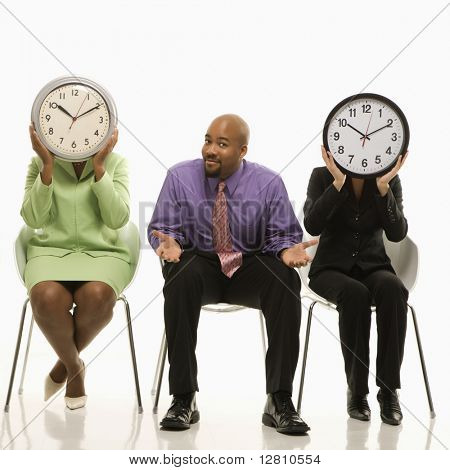 Businesswomen sitting holding clocks over faces while African-American businessman shrugs.