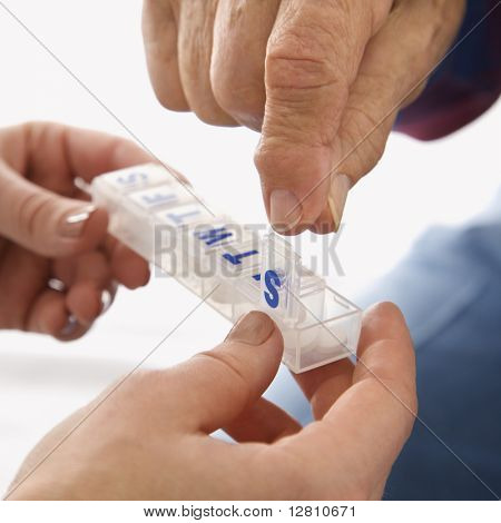 Mid-adult Caucasian female hands holding medication case for  an elderly Caucasian male.