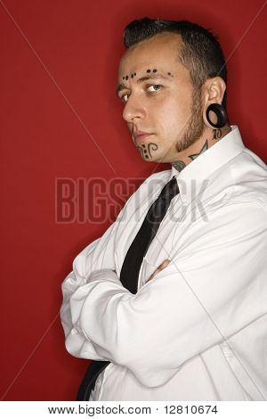 Caucasian mid-adult man with tattoos and piercings wearing necktie looking at viewer.