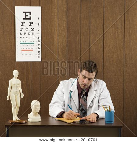 Mid-adult Caucasian male doctor sitting at desk writing.