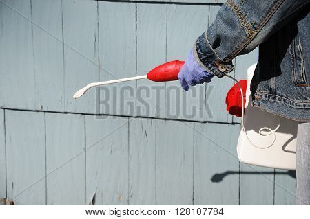 outdoor worker spray pesticide on the house exterior