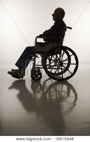 Profile view of silhouetted Caucasion elderly man sitting in wheelchair.