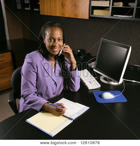 African-American young adult business woman talking on cell phone and writing in planner in office smiling and looking at viewer.