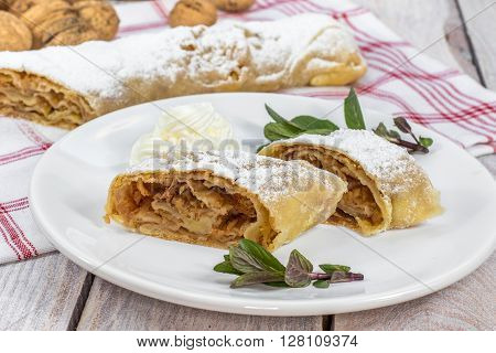 Two Slices Homemade Apple Strudel on Plate with Whipped Cream and Mint