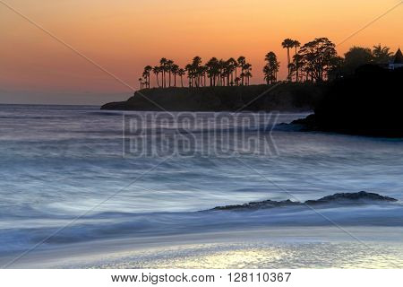 vibrant sunset at the beach slow shutter for motion blur on the water. Selective focus on trees and rocks in water