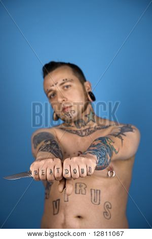Barechested Caucasian mid-adult man with tattoos and piercings holding knife.