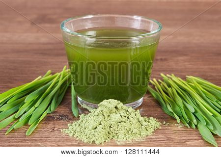 Heap of young powder barley barley grass and beverage on wooden background healthy nutrition and lifestyle body detox