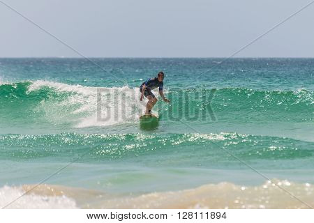 Manly Australia - November 9 2014: A man rides his surfboard towards the shore. Seven miles from the heart of Sydney famous Manly beach offers a wide range of sports and recreational activities.