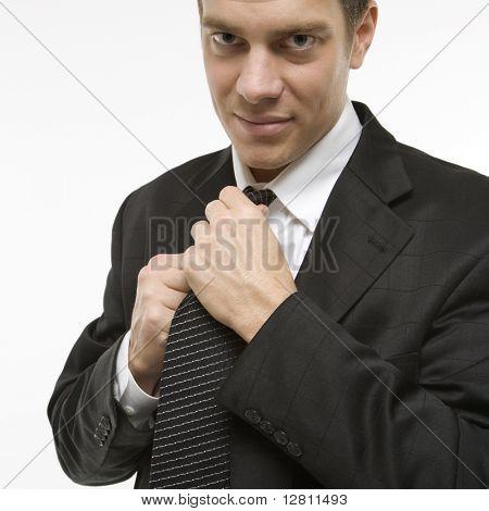 Caucasian mid-adult man straightening necktie.