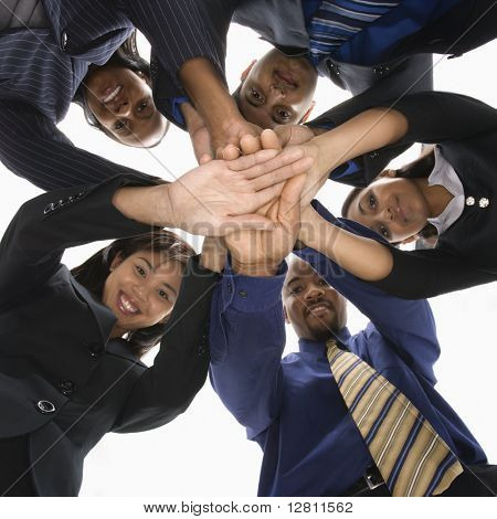 Retrato de grupo empresarial multiétnica de hombres y mujeres con manos en huddle en ángulo bajo.