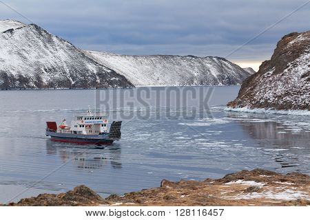 Icebreaking ferries arriving at Baikal port in the twilight of short polar day