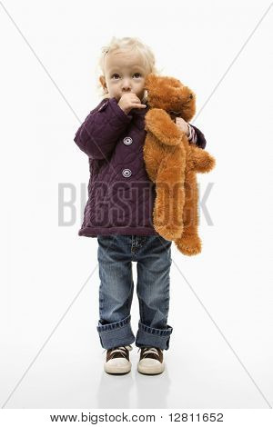 Young Caucasian female toddler sucking her thumb and holding her teddy bear.