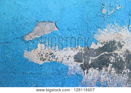 Blue painted grunge concrete wall. Weathered peeling paint texture. Blue weathered background. Bright blue paint texture cracked over time.