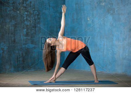 Sporty Beautiful Young Woman Doing Trikonasana