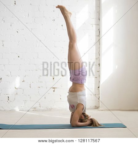 Woman Doing Headstand In Sunny Room