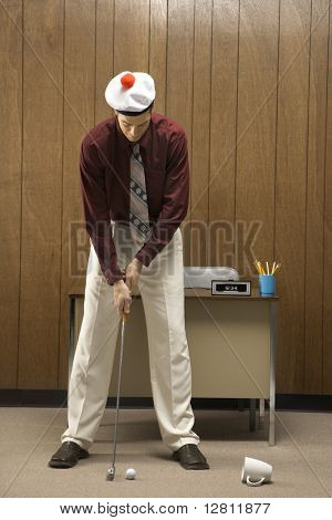 Caucasion mid-adult retro businessman wearing cap putting golf ball into coffee cup in his office.