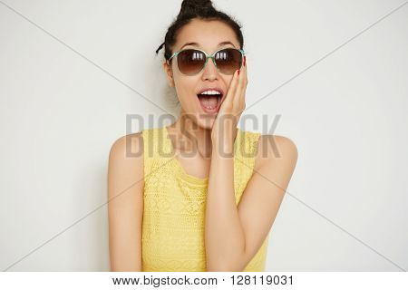 Cropped Isolated Shot Of Surprised Young Brunette Female Wearing Sunglasses And Yellow Top, Mouth Wi