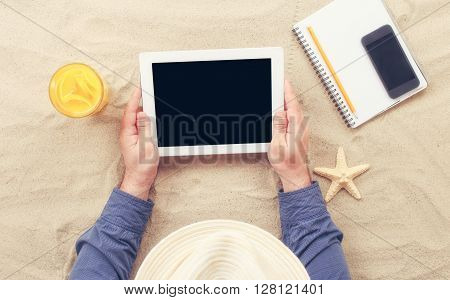 Man holding tablet with blank screen lying on the beach. Man working using a tablet computer on the beach. Concept of work outside of the office. Top view