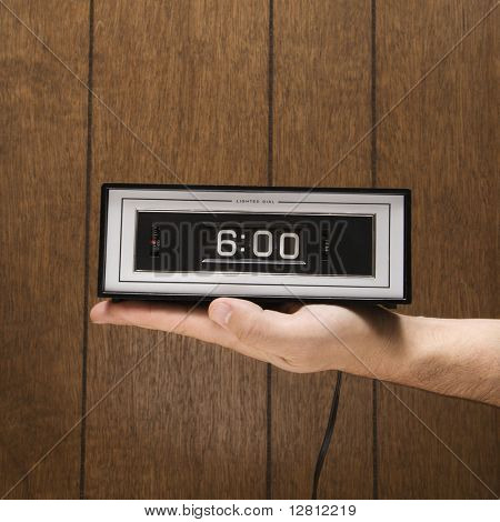 Caucasion male hand holding retro clock set for 6:00 against wood paneling.