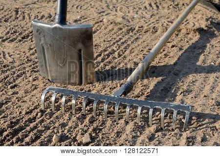 Rake and spade on loosened soil closeup