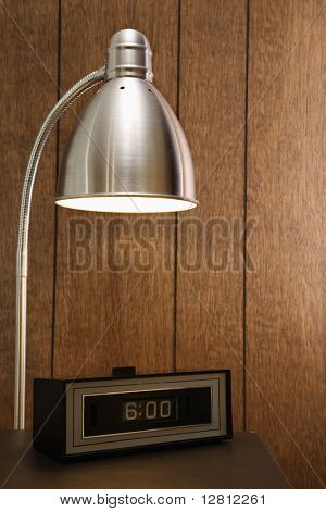 Retro scene of desk lamp shining on retro clock set for 6:00 against wood paneling.