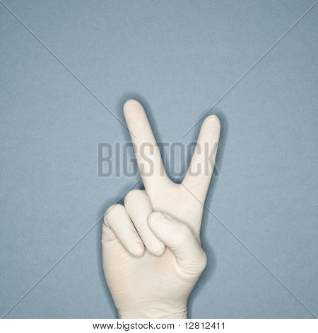 Hand wearing white rubber glove making a gesture meaning peace.