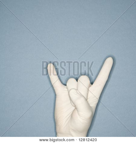 Hand wearing white rubber glove making gesture.