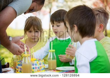 Happy sweet preschool children friends and relatives celebrating fifth birthday of cute boy outdoor in blooming apple tree garden springtime late afternoon ** Note: Soft Focus at 100%, best at smaller sizes