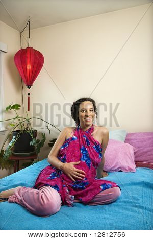 Portrait of expecting female with hands on stomach in bedroom.