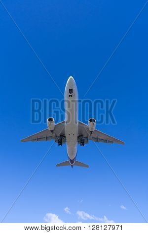 Jet passenger airplane approaching an airport for landing, view from below