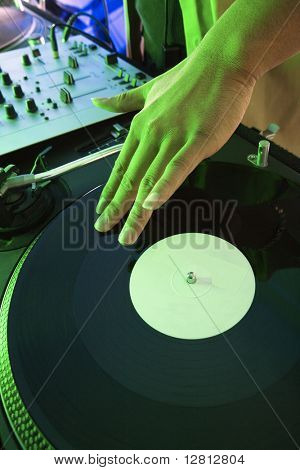 Close-up of Asian young adult male DJ's hand spinning vinyl record.