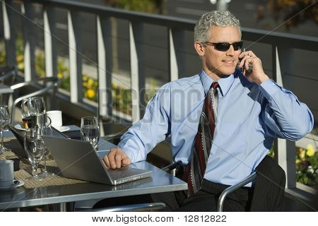 Prime adult Caucasian man in suit sitting at patio table ouside with laptop and talking on cellphone.