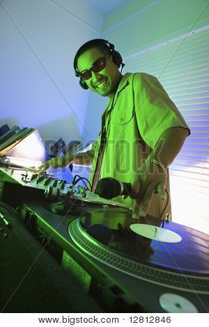 Asian young adult male DJ wearing sunglasses behind mixing equipment with hand on record turntable looking at viewer smiling.