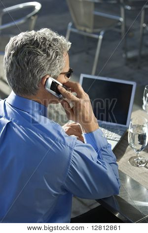 Rear view of prime adult Caucasian man in suit talking on cellphone and looking at laptop.