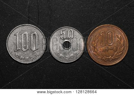 1,50,100 Japanese yen coins on black color background
