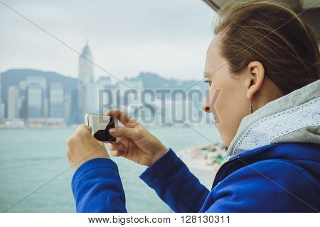 Young Woman Makes The Photo On The Phone Dressed In A Fashionable Blue Coat In Hong Kong.