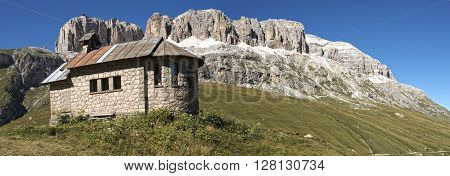 Church on the green grass at the foot of the massif of the Sella mountain range and blue sky in the background