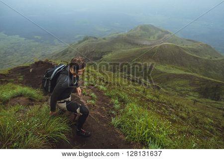 Hiker Man Climbing A Steep Wall In Mountain
