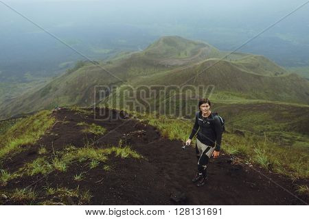 Portrait of hiker man posing on the mountain freedom concept. Ascent to the volcano