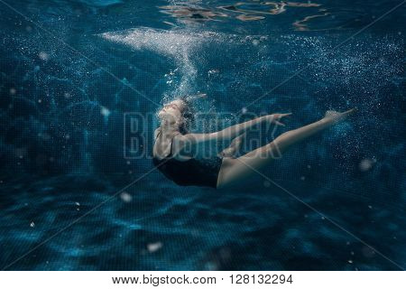 Woman dancing under the water around the air bubbles.
