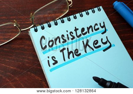 Consistency is The Key written on a notepad with marker.