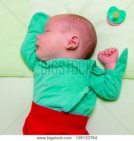 Sleeping baby with nipple, contrast of colors