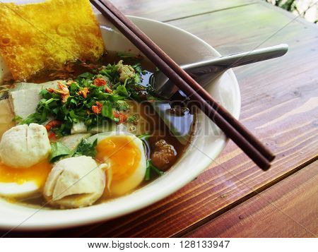a bowl of noodle soup with egg and crispy wonton
