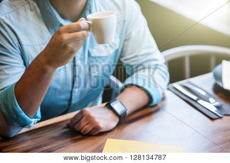Close up of arms of man drinking coffee in cafe. He is sitting at table. Focus on a cup in his hand