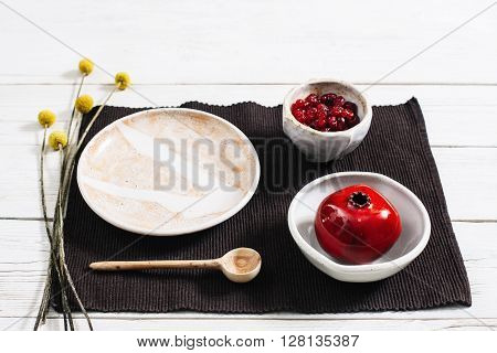 Pottery ceramics set with red decorative pomegranate. Dried fruits in clay plate top view over white wood table. Beige crockery on white wooden background flat lay.