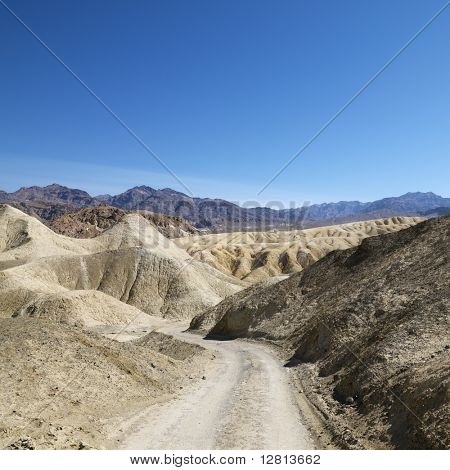 Dirt road through barren landscape in Death Valley National Park.