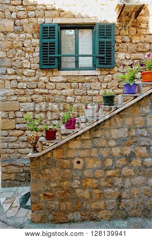 Ulcinj Stari Grad alley with venetian blinds and colorful pots flowered , Montenegro
